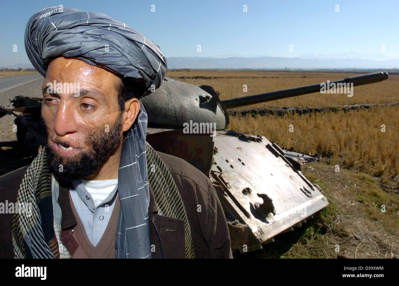 (dpa) - An Afghan victim of war, the 40-year-old Ex-Mujahideen Dadguhl Delawan, stands in front of a Russian tank - Stock Image
