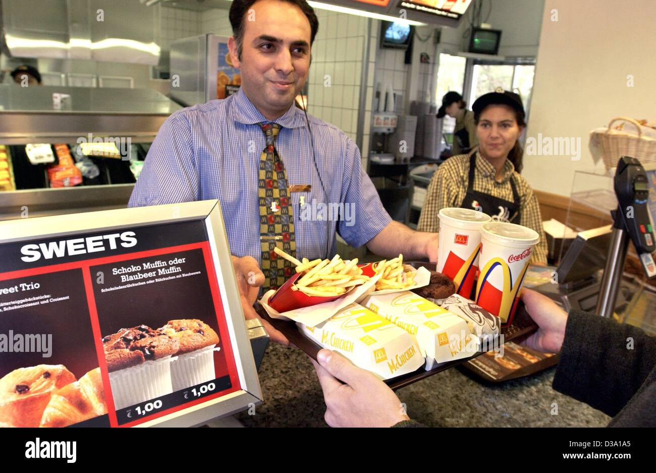 (dpa) - A McDonald's employee is handing over a tray of food to a customer at one of the chain's fast-food - Stock Image