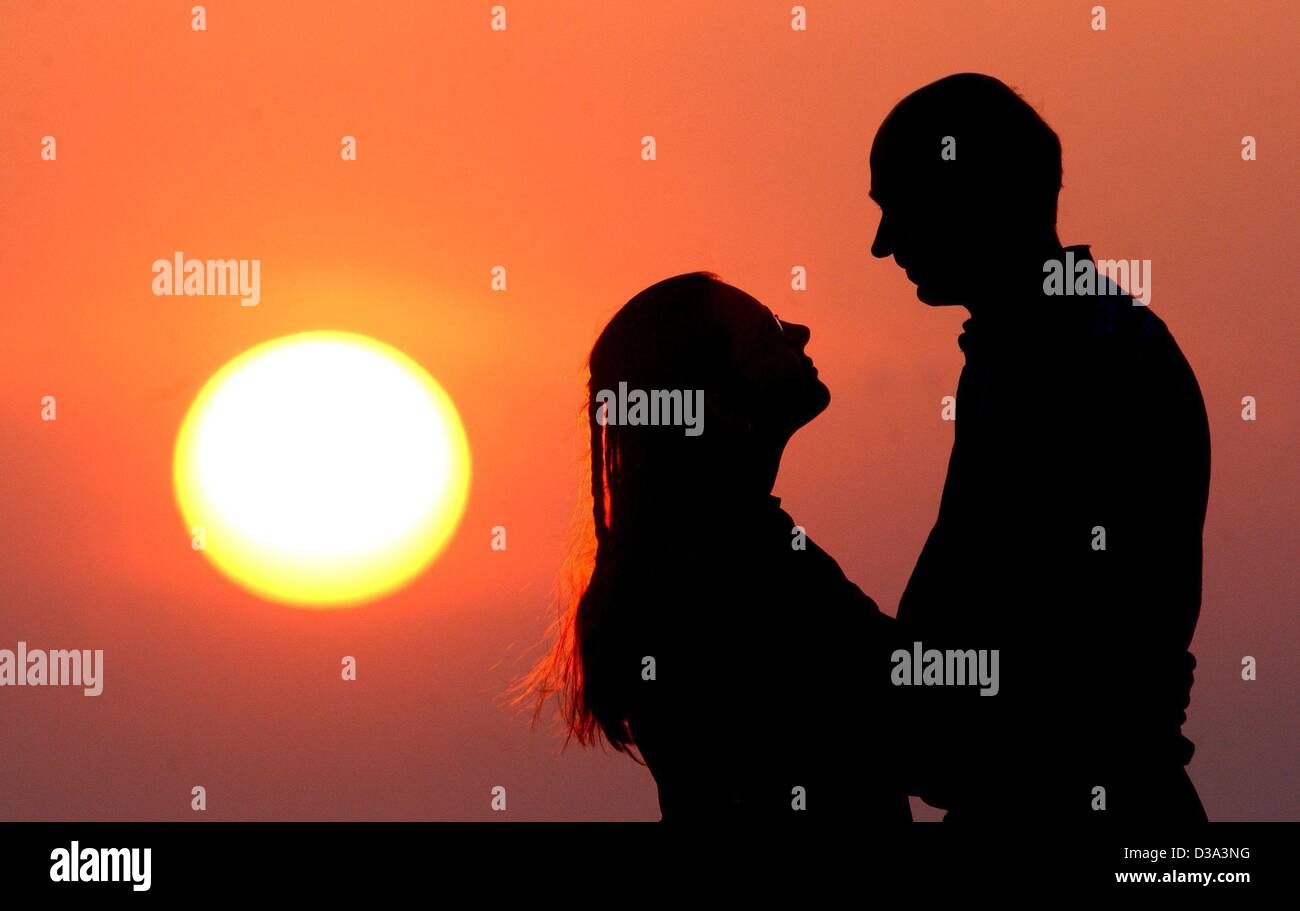 (dpa) - The silhouette of a love couple appears as the sun sets near Lebus, east Germany, 1 April 2002. - Stock Image