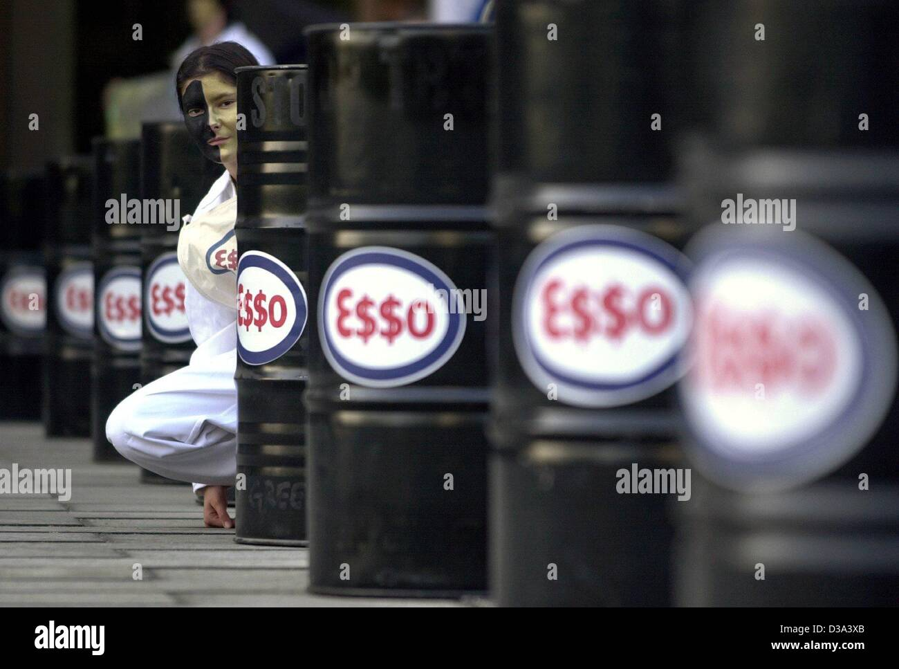 (dpa) - A Greenpeace activist sits behind the oil barrels with the logo E$$O of the company Exxon Mobil during a - Stock Image