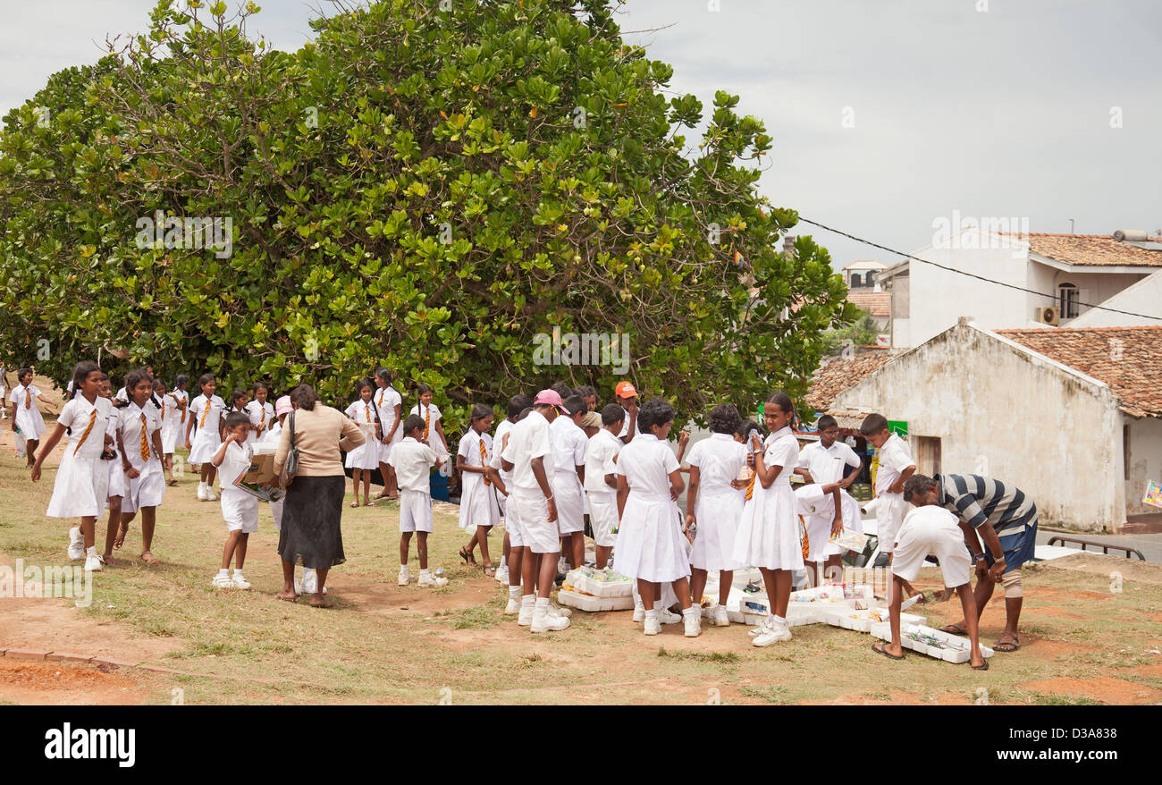 School students on a school trip to Galle Fortress. They are choosing souvenirs like posters, small toys and wristlets. - Stock Image