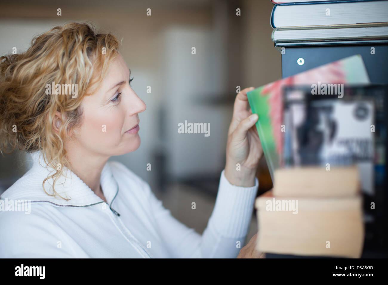 Woman organizing bookshelf - Stock Image