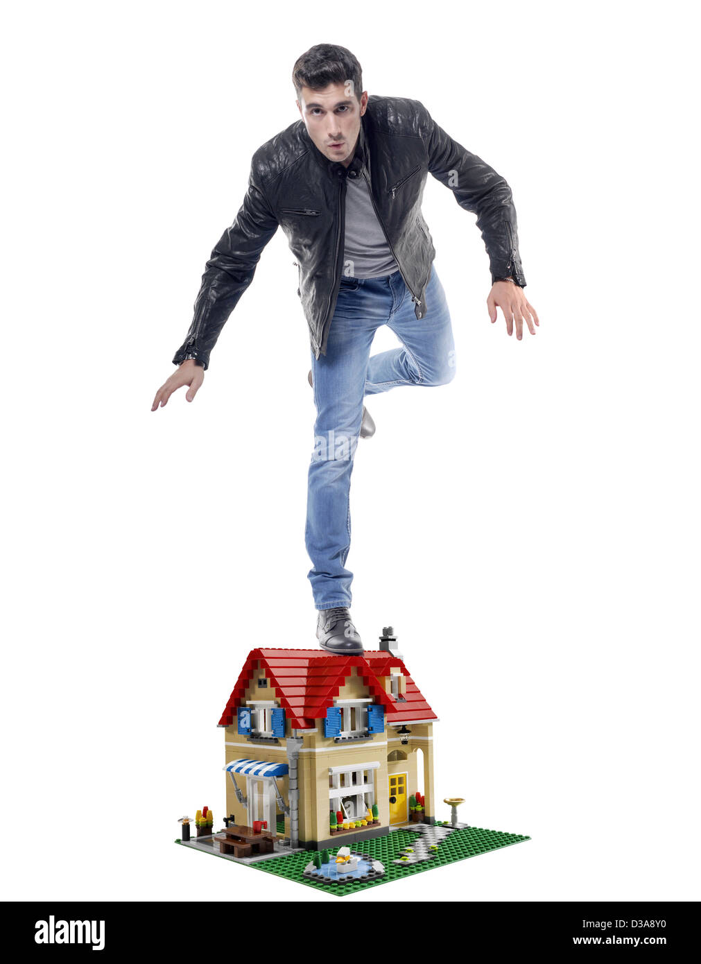 Man balanced on a small model of a house - Stock Image