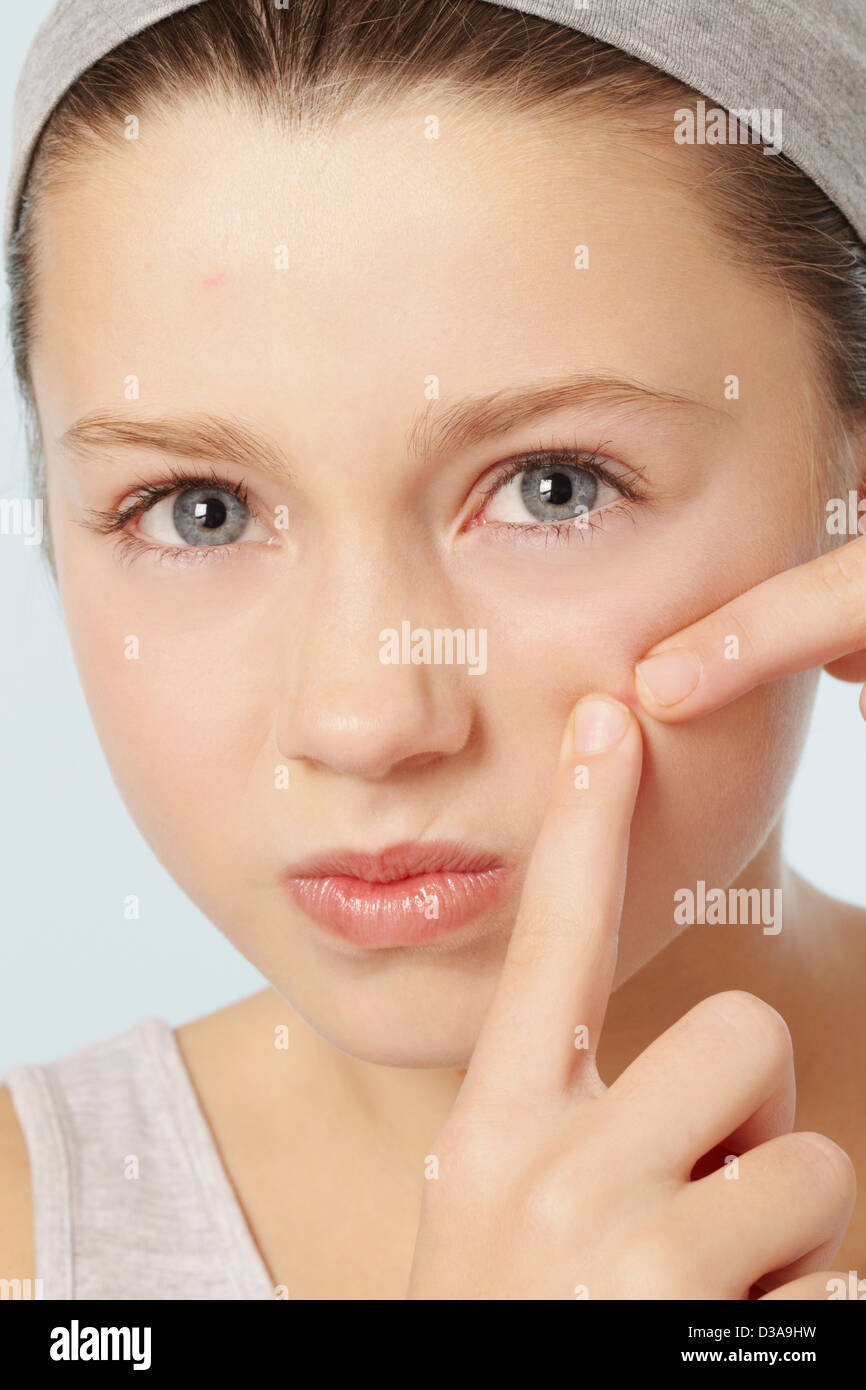 Girl squeezing spot on her face - Stock Image