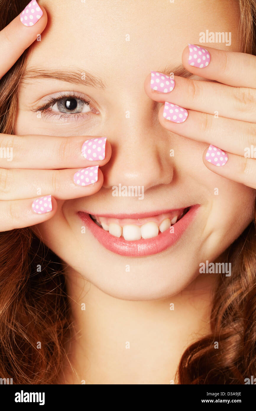 Smiling girl with polka dot manicure - Stock Image