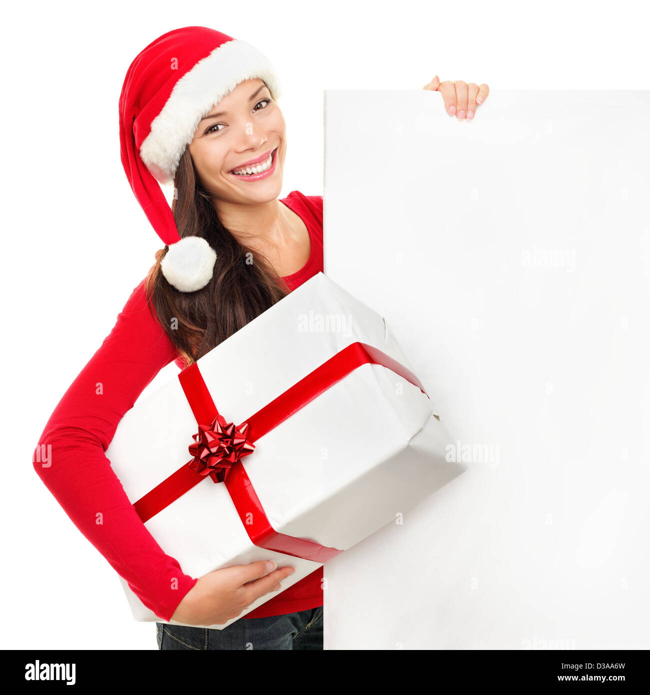 Portrait of happy beautiful Christmas young woman in Santa hat holding empty board sign and present isolated on - Stock Image