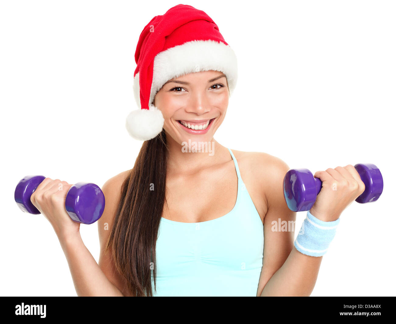 Portrait of happy mixed race young female fitness model woman wearing Santa hat lifting dumbbells isolated on white - Stock Image