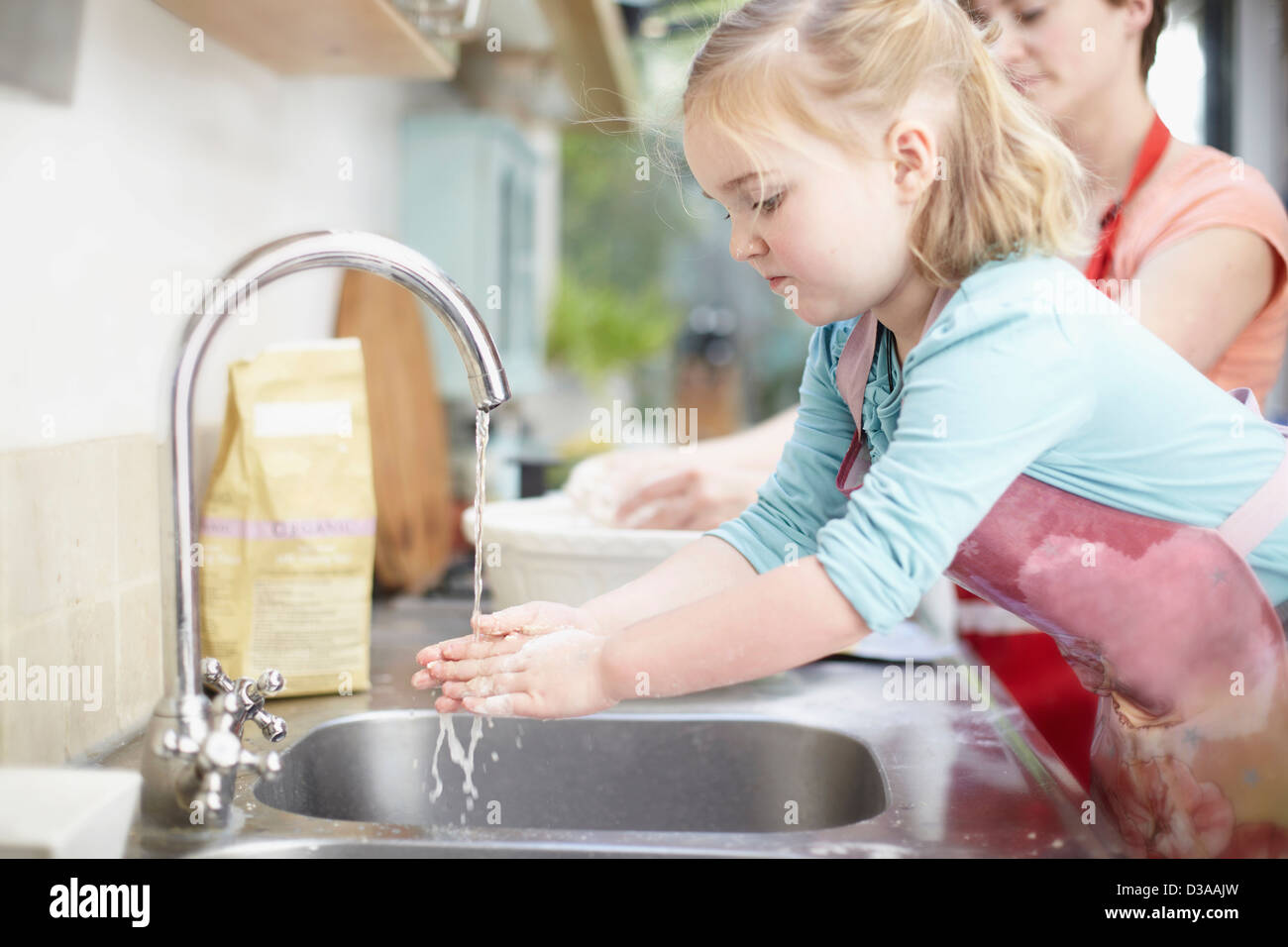 Girl washing her hands in kitchen - Stock Image