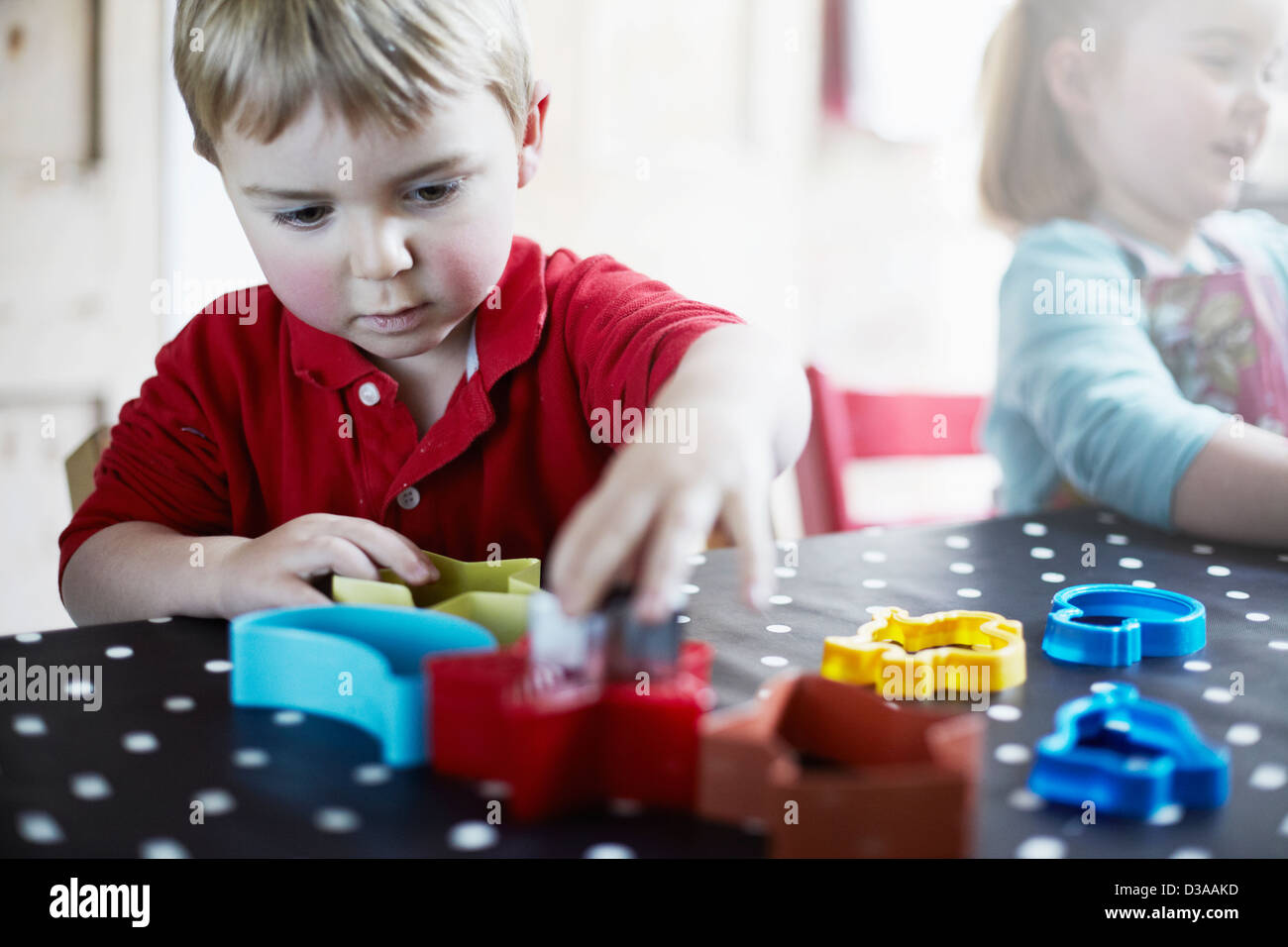 Children playing with shapes on table Stock Photo