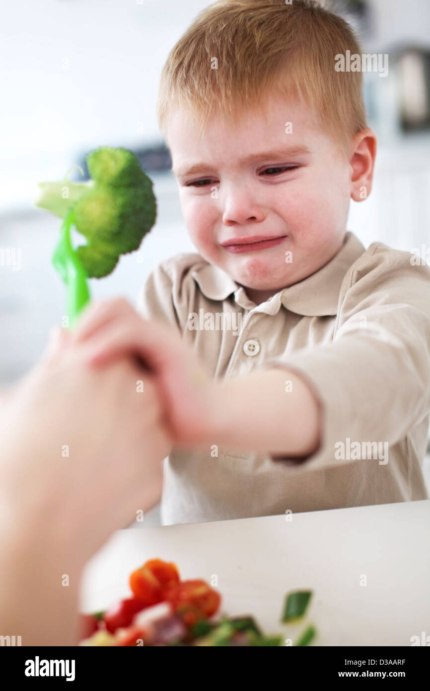 Crying boy refusing broccoli in kitchen - Stock Image