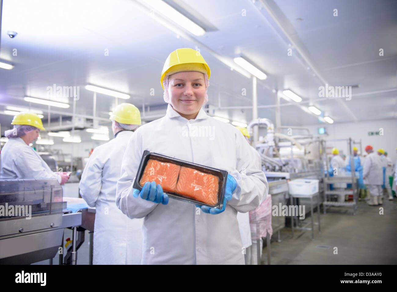 Portrait of worker holding pack of salmon fillets in food factory - Stock Image