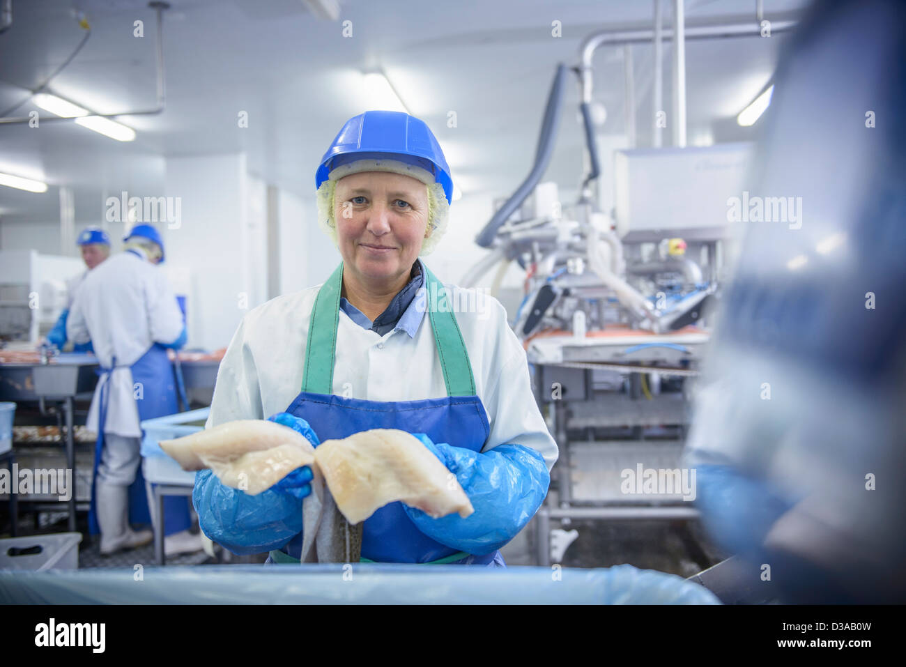 Portrait of worker holding fresh fish fillets in food factory - Stock Image