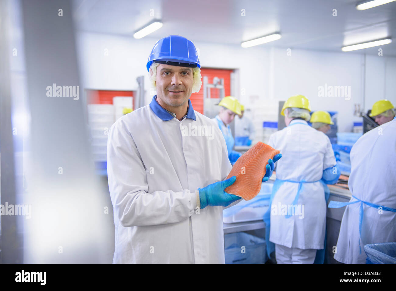Portrait of worker holding salmon fillet in food factory, smiling - Stock Image