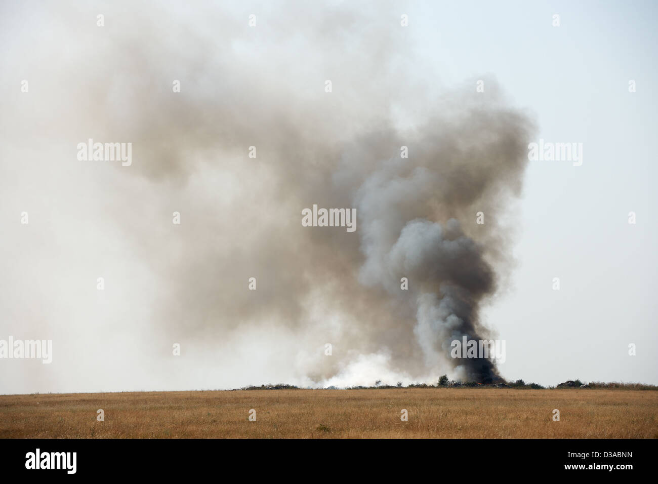 Toxic black smoke from fire in dung-hill emitting poison in the air Stock Photo