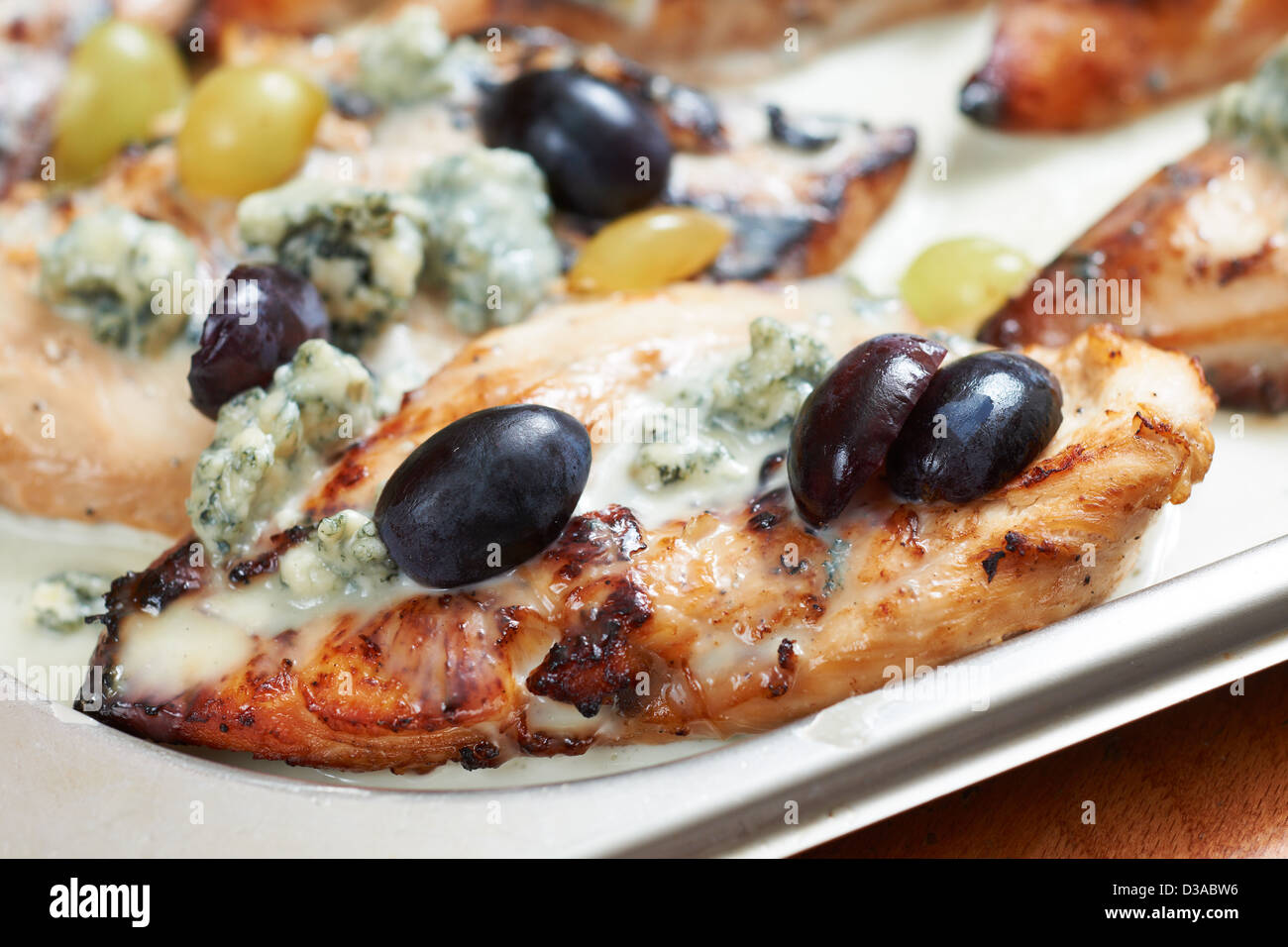 Mediterranean food of Provence, chicken fillet roasted with blue cheese, grapes and olives - Stock Image