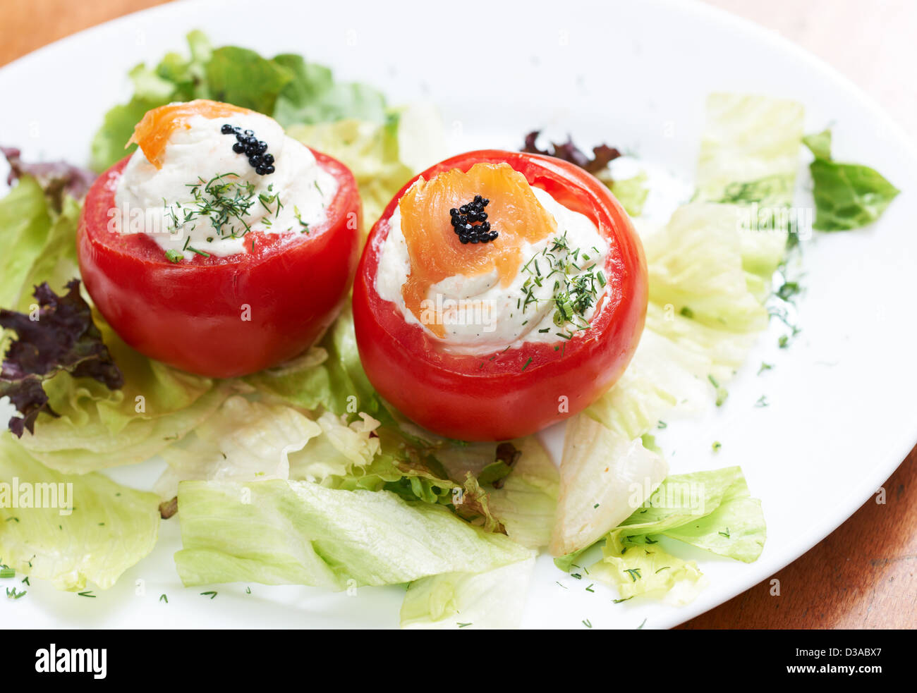Tomatoes stiffed with roe spread and decorated with salmon fillet and black caviar - Stock Image