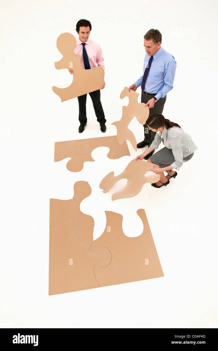 Business people assembling puzzle - Stock Image
