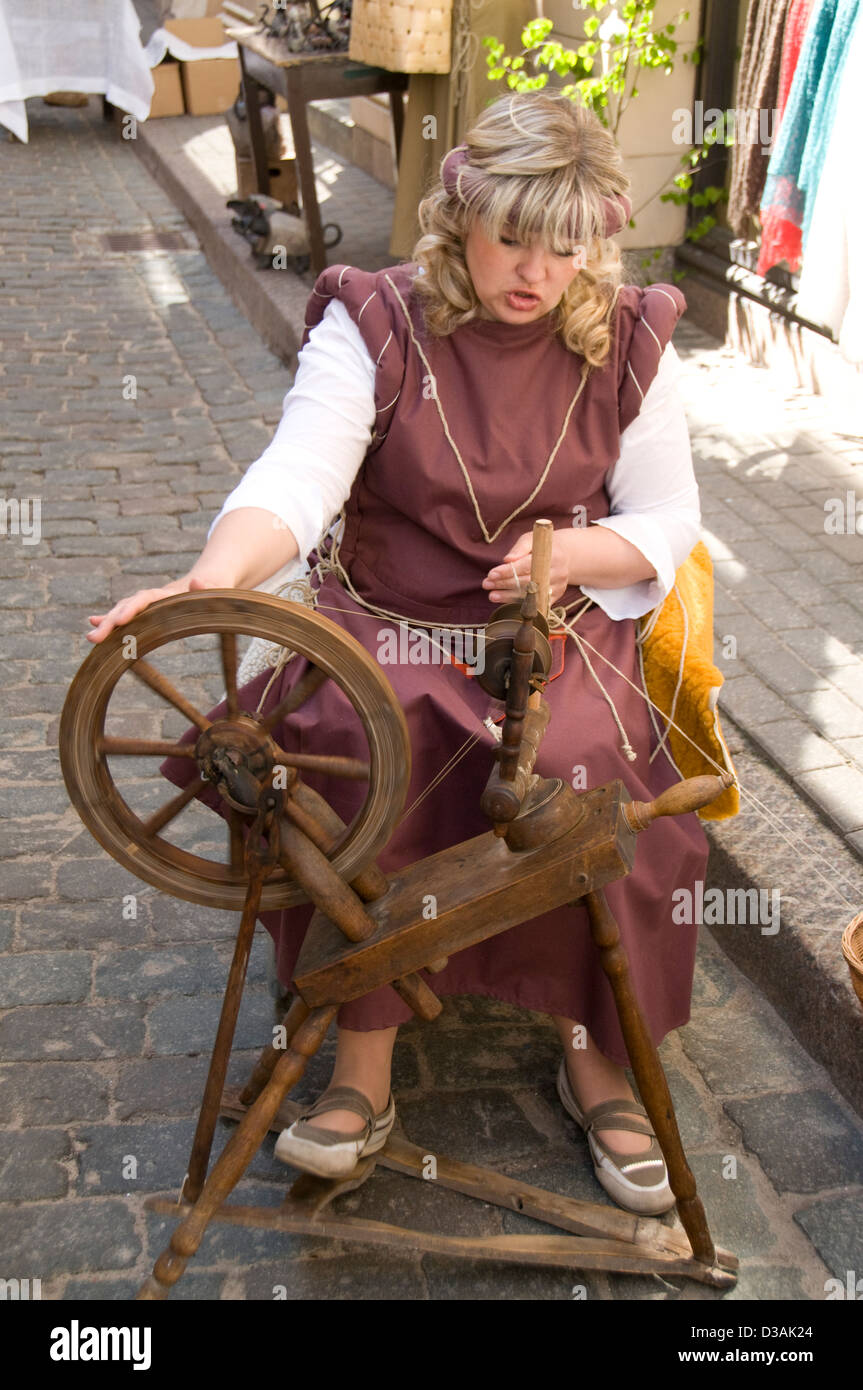A wool spinner taking part in the old Latvain culture show in Amatu iela,Riga old town,Riga,Latvia Baltic States - Stock Image