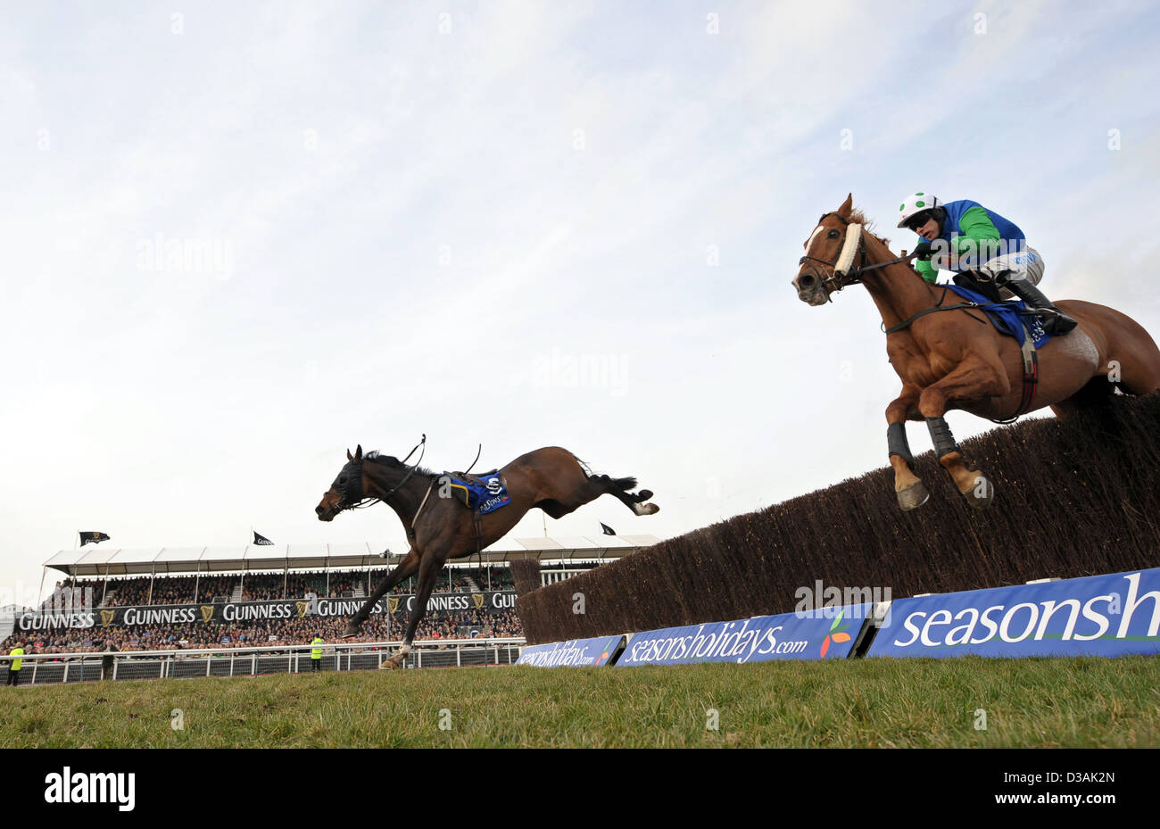 Horses jump a fence during The Cheltenham Festival an annual horse racing event in England Stock Photo