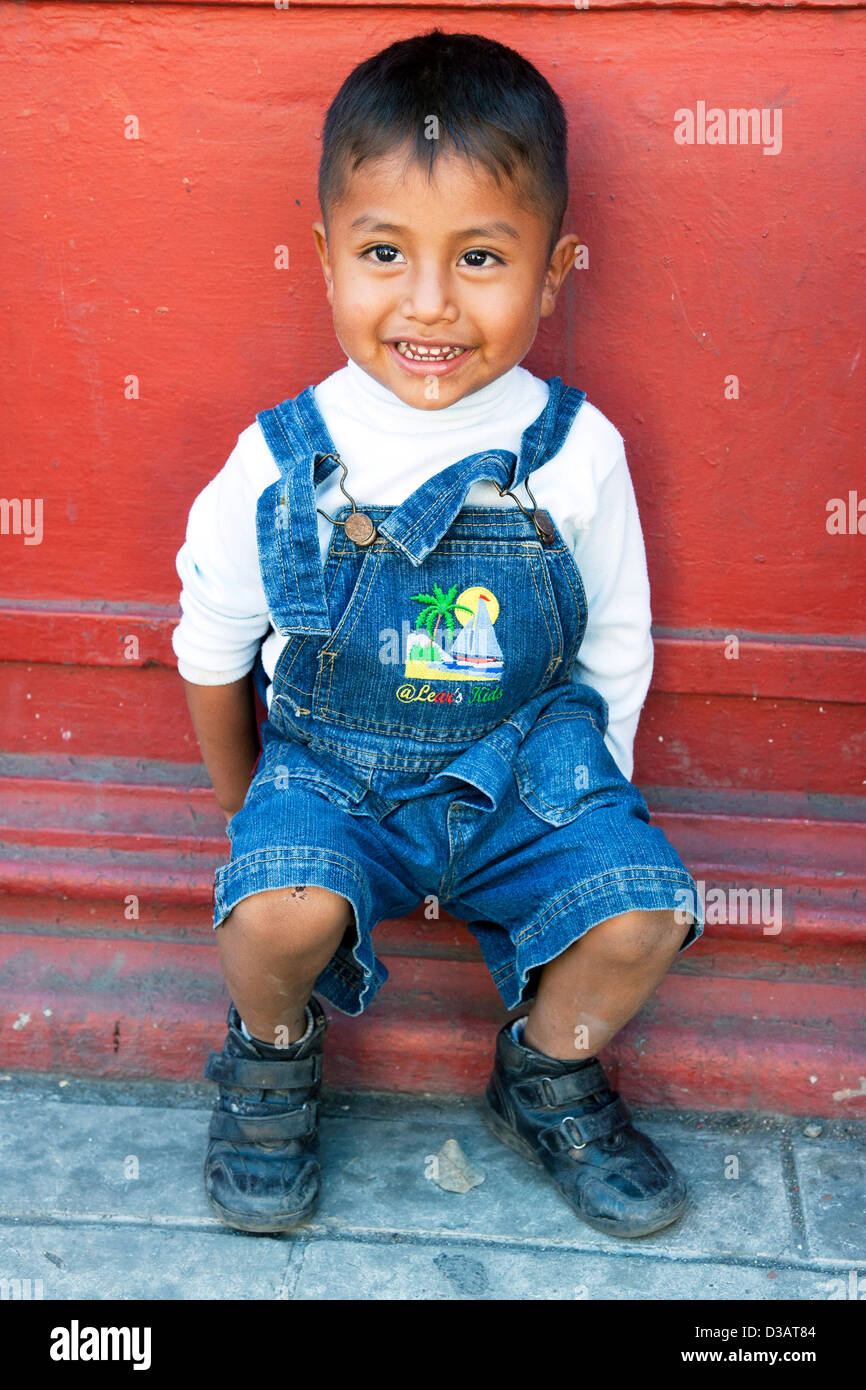 mischievous bright eyed smiling little Mexican boy sits outside against deep red wall on a street in Oaxaca de Juarez - Stock Image