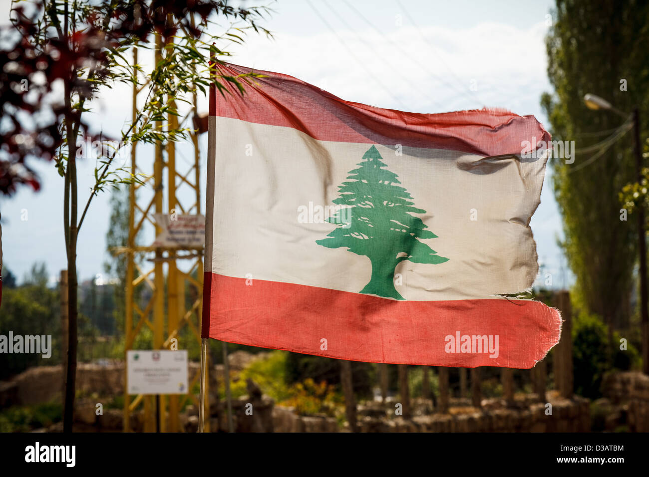 Tattered Lebanese flag floating in the wind in the Hezbollah controlled Beqaa Valley. - Stock Image