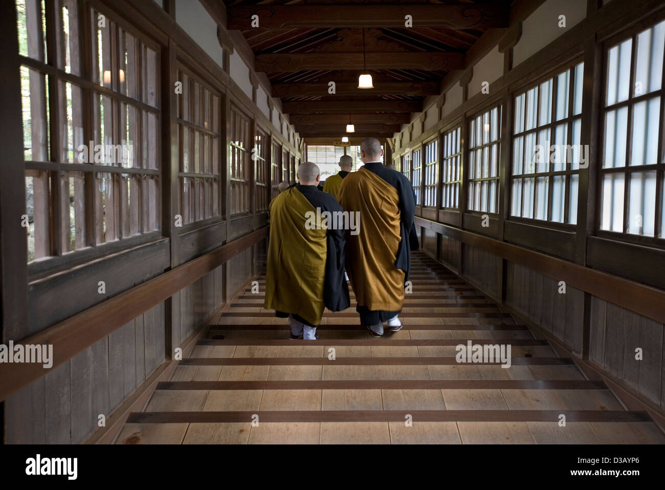Bald-headed Buddhist monks wearing robes walking through covered stairway at Soto sect Eiheiji Temple in Fukui, - Stock Image