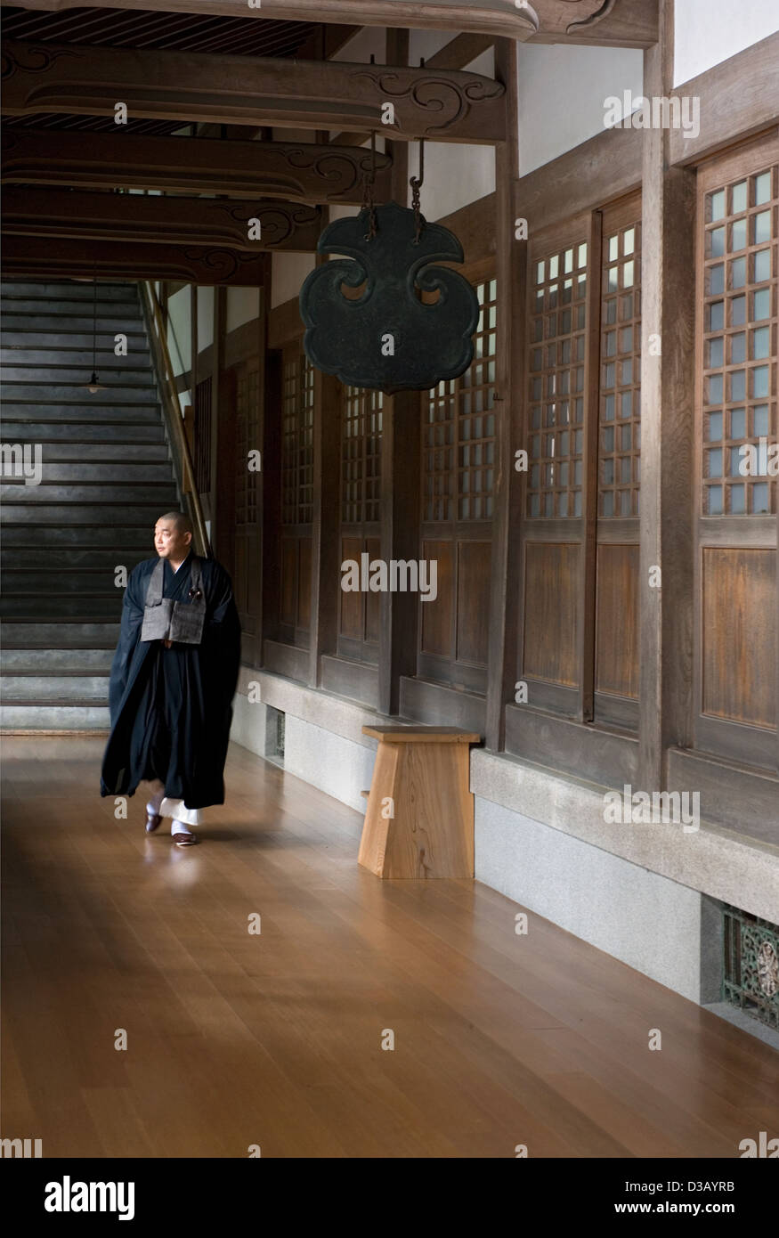 A Soto sect monk in flowing robes walks past a bronze gong inside the Zen Buddhist Eiheiji Temple in Fukui Prefecture. - Stock Image