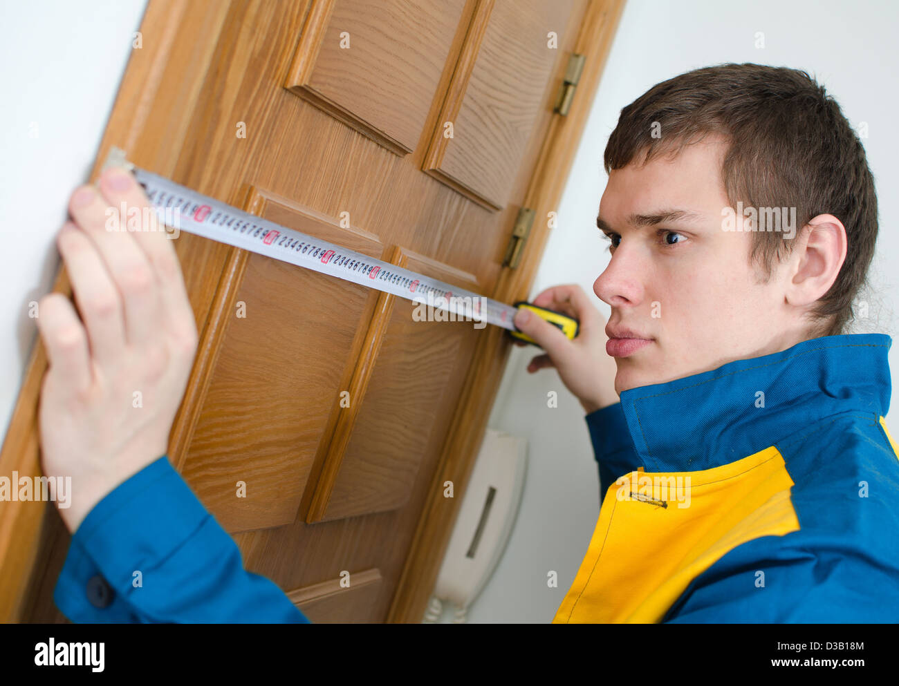 Young handyman in uniform working with measure tape Stock Photo