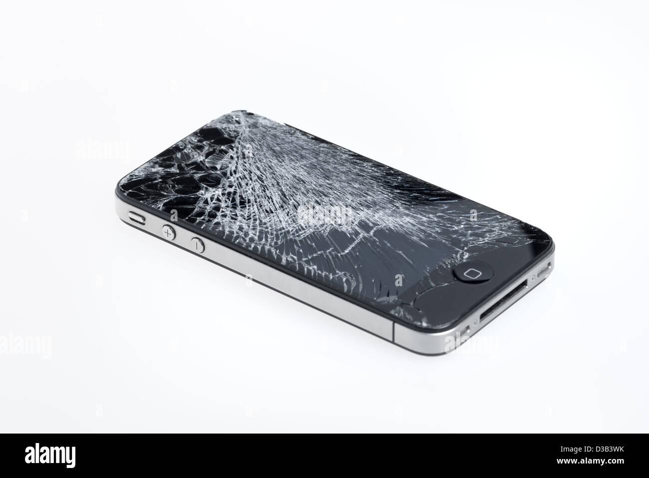 The old Apple iPhone 4 with broken screen, studio shot. - Stock Image