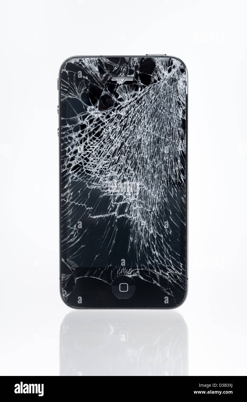 The old Apple iPhone 4 with crashed screen, studio shot. - Stock Image