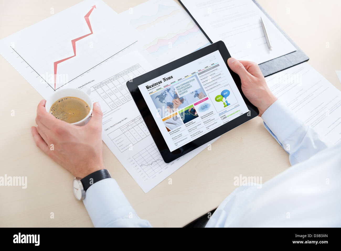 Businessman at workplace drinking coffee and looking latest business news on modern digital computer. - Stock Image