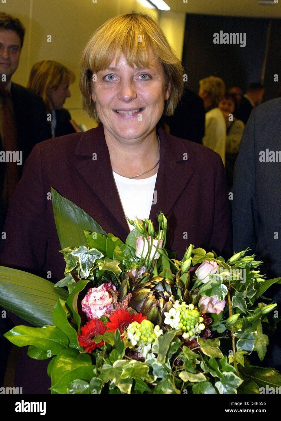 (dpa) - Angela Merkel, chairwoman of the CDU and newly elected leader of the CDU fraction in the Bundestag, holds a bouquet of flowers and smiles at the photographers, Berlin, 24 September 2002. 214 MPs of the CDU/CSU fraction voted for the 48-year-old, 18 voted 'no', eleven votes were invalid. Ange Stock Photo