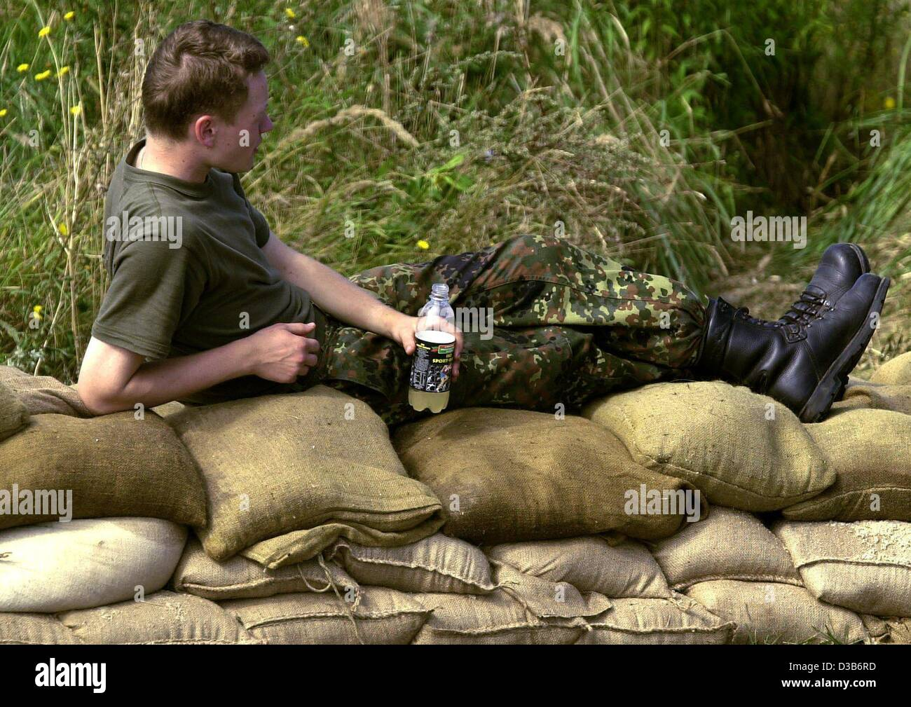 (dpa) - A soldier in charge of fighting the flood in Bitterfeld, Germany, rests on a sandbag barrier, 16 August - Stock Image