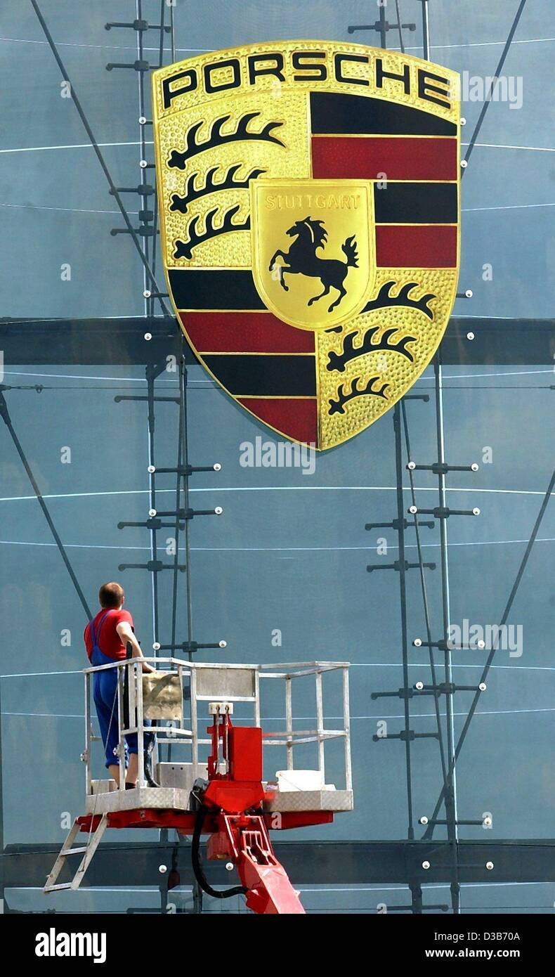 (dpa) - A seven square metre large Porsche logo is being pulled up a 24 metre high glass pylon near the German automotive - Stock Image