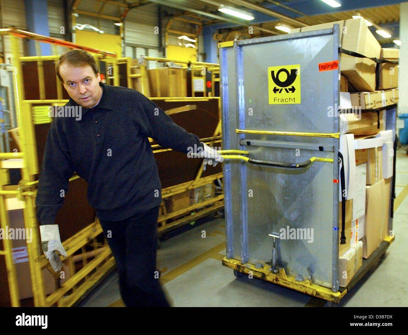 (dpa) - Employee Helmut Gast draws a carrier for parcels in the parcel delivery centre of the Deutsche Post in Rostock, - Stock Image