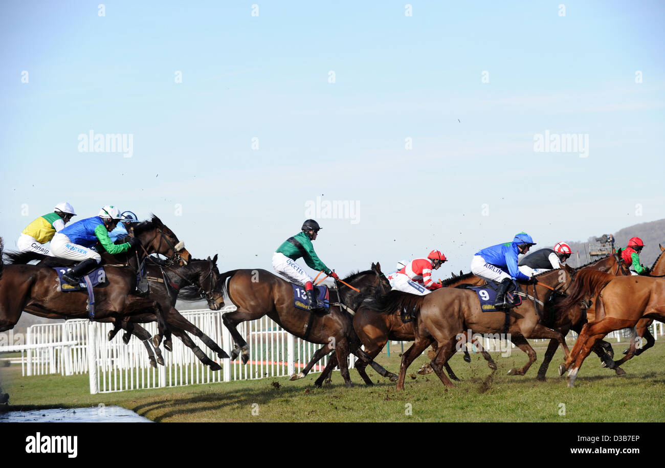 Jockeys jump their horses over a fence during The Cheltenham Festival an annual horse racing event in England Stock Photo