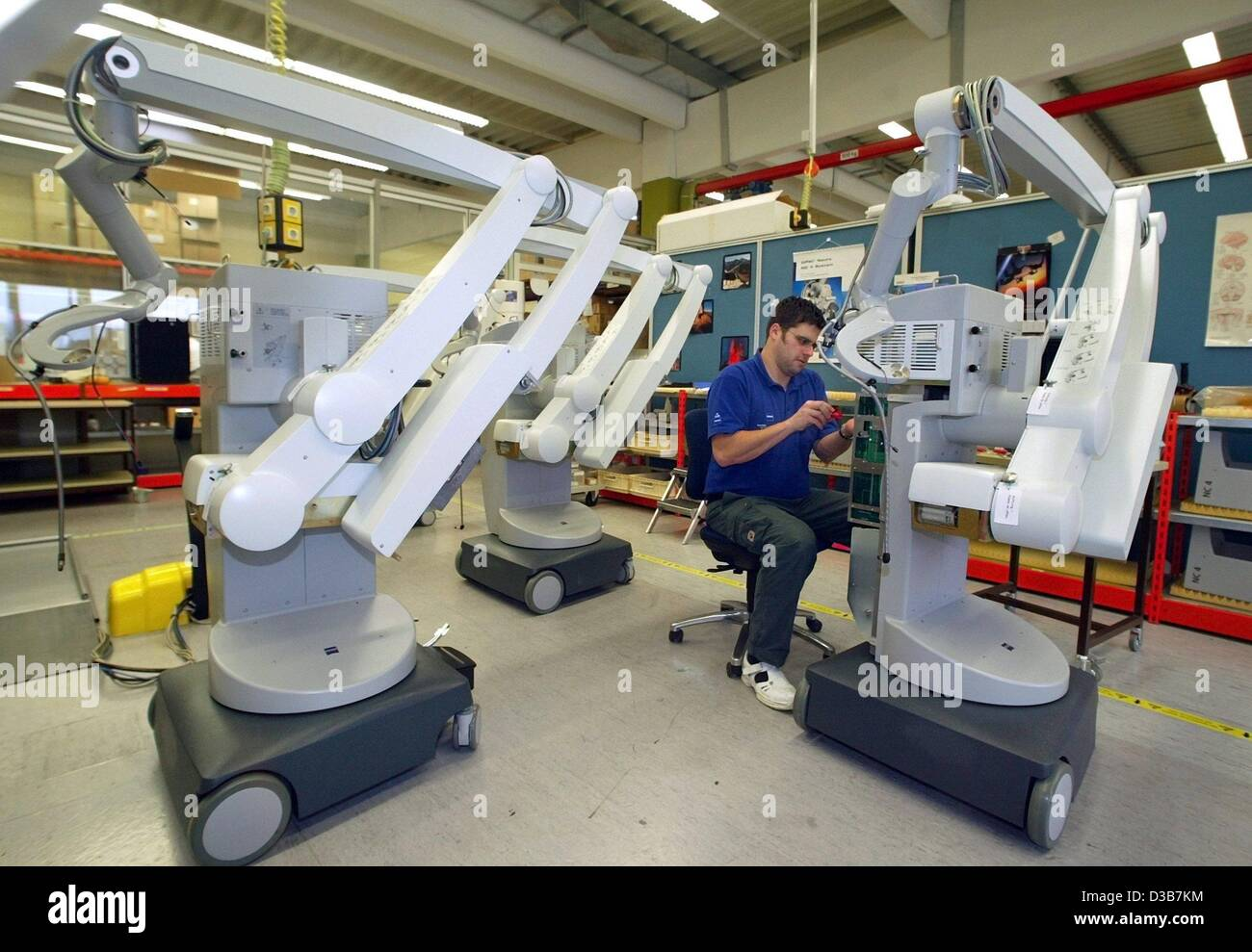 dpa) - An employee of Carl Zeiss is working on tripods for