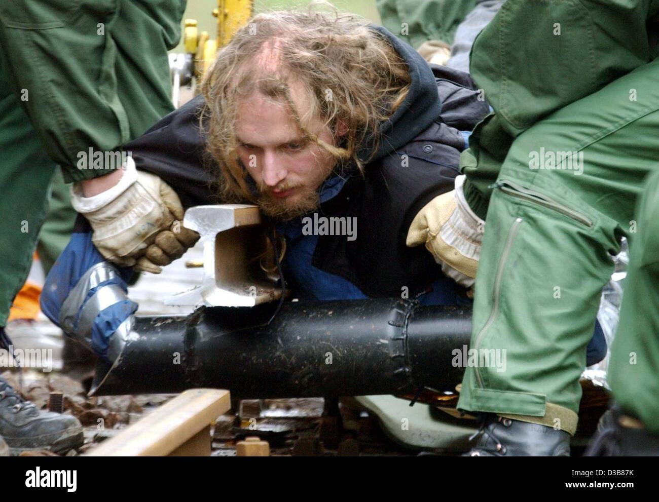 (dpa) - Policemen remove a protestor against the current nuclear waste transport who has chained himself to a steel - Stock Image