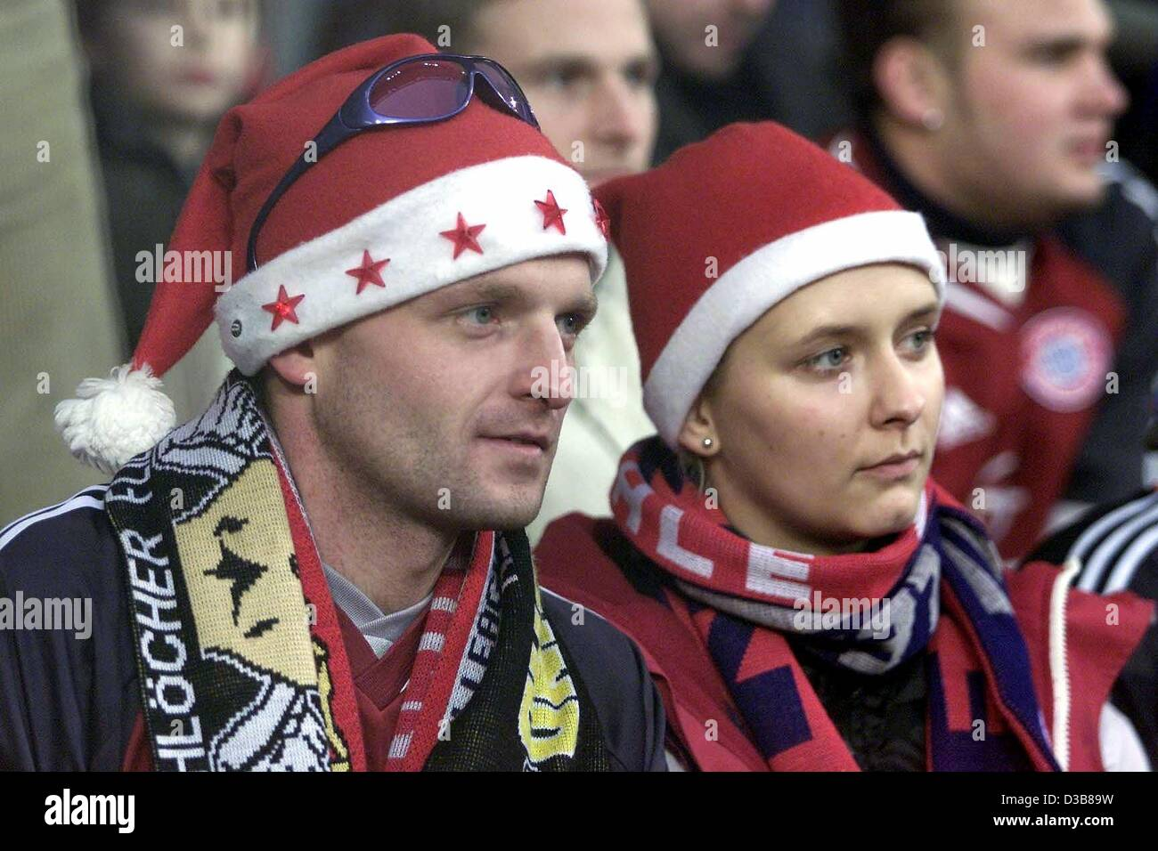 Two fans of the VfB Stuttgart dressed with Santa Claus caps follow the premier league match between the VfB Stuttgart - Stock Image
