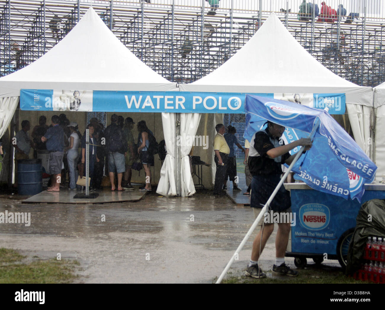 (dpa) - Spectators seek shelter underneath two marquees from a heavy downpour at the entrance to the water polo - Stock Image