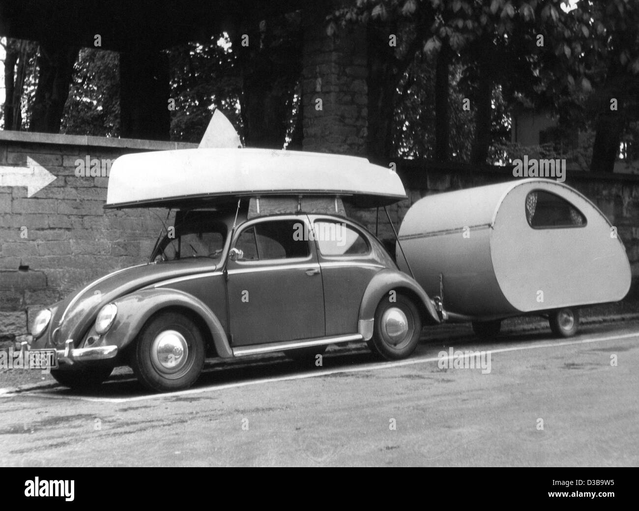 (dpa files) - A VW Beetle loaded with a sailing boat and a hitched caravan is ready for the holiday trip, West Germany, - Stock Image
