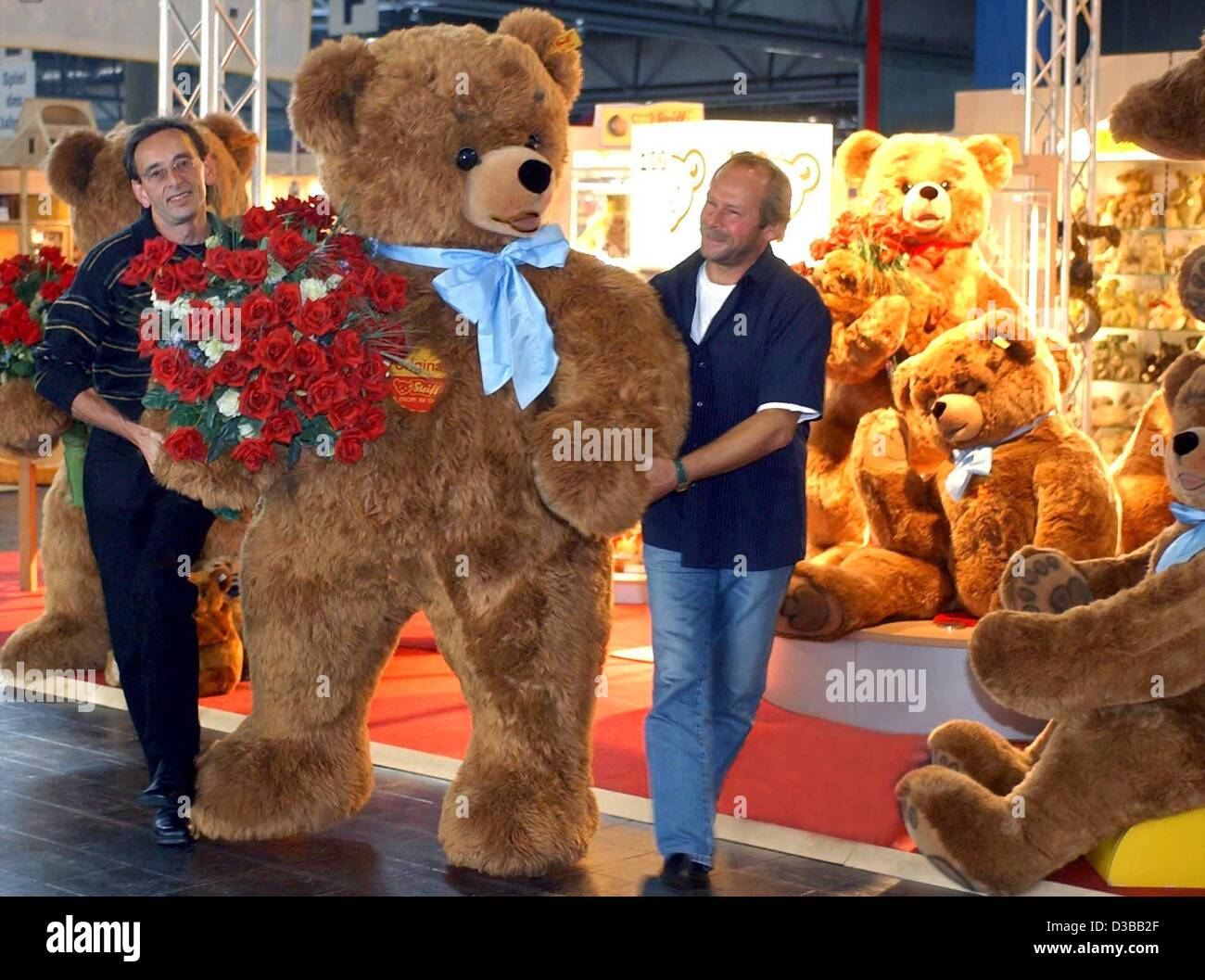 (dpa) - Two men arrange a two-meter large teddy bear of the brand 'Steiff' at a toy trade fair in Leipzig, - Stock Image