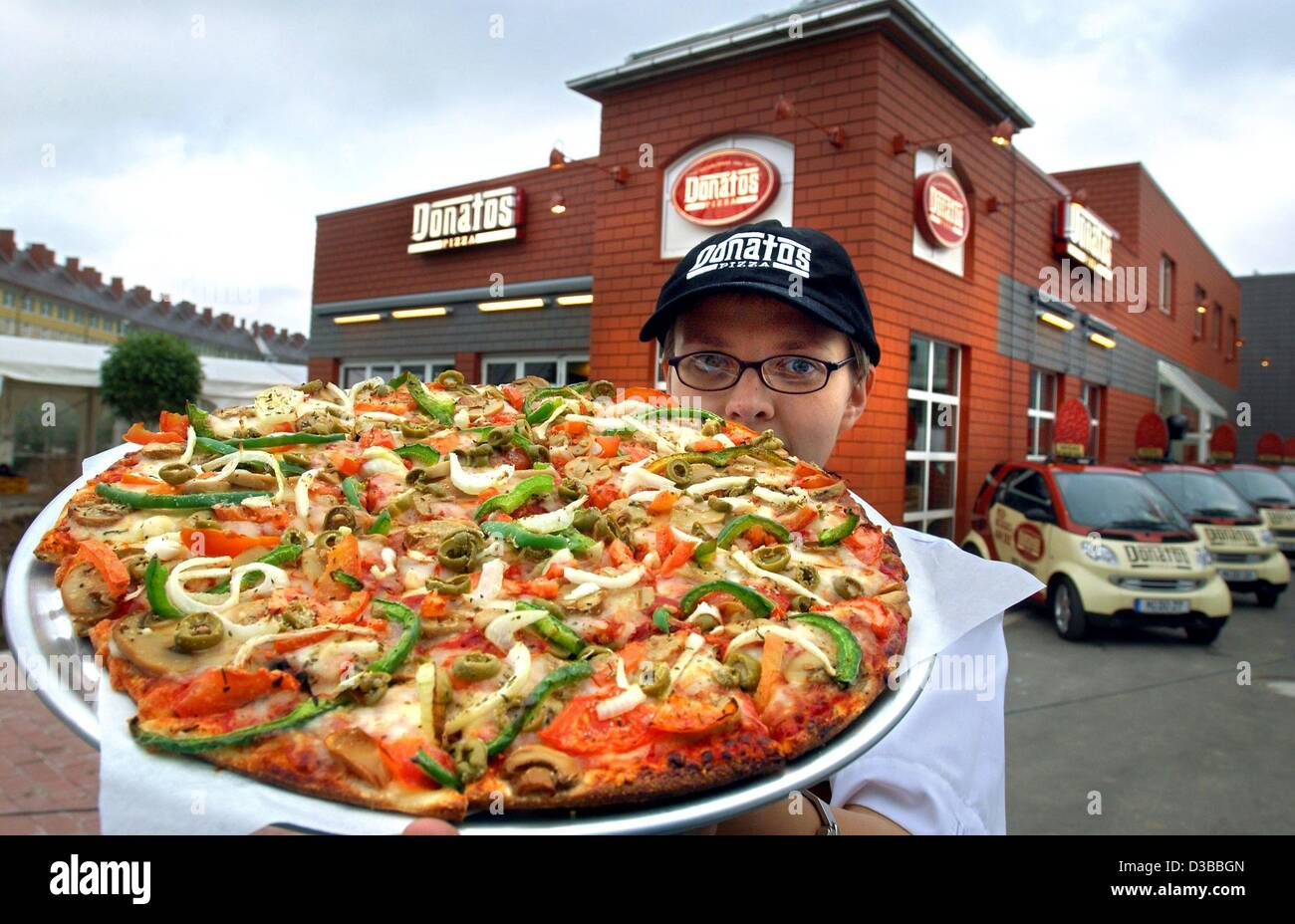 (dpa) - An employee of the pizza chain 'Donatos' stands in front of the first German subsidiary in Munich - Stock Image