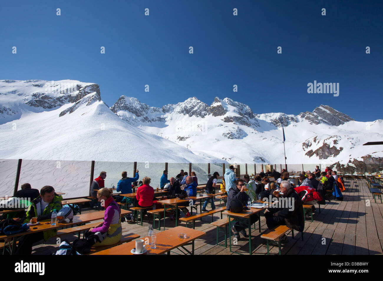 Skiers having lunch on the terrace of a mountain restaurant above Zurs, Arlberg, Austria. - Stock Image