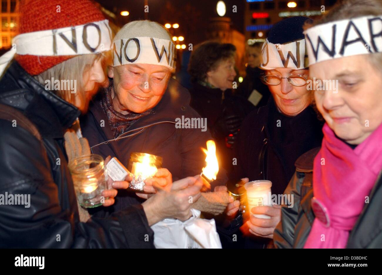 (dpa) - Protesters wear headbands with the writing 'no war' and light candles during a demonstration against - Stock Image