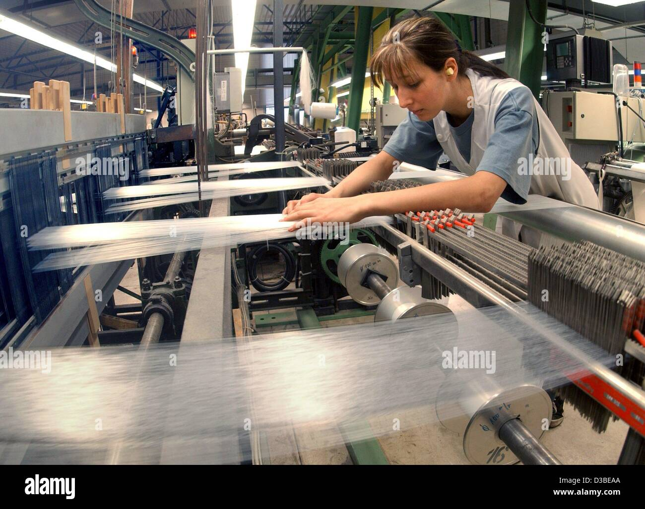 (dpa) - A worker oversees the production of cloth made from natural silk at the Plauener Spinnhuette GmbH (Plauener - Stock Image