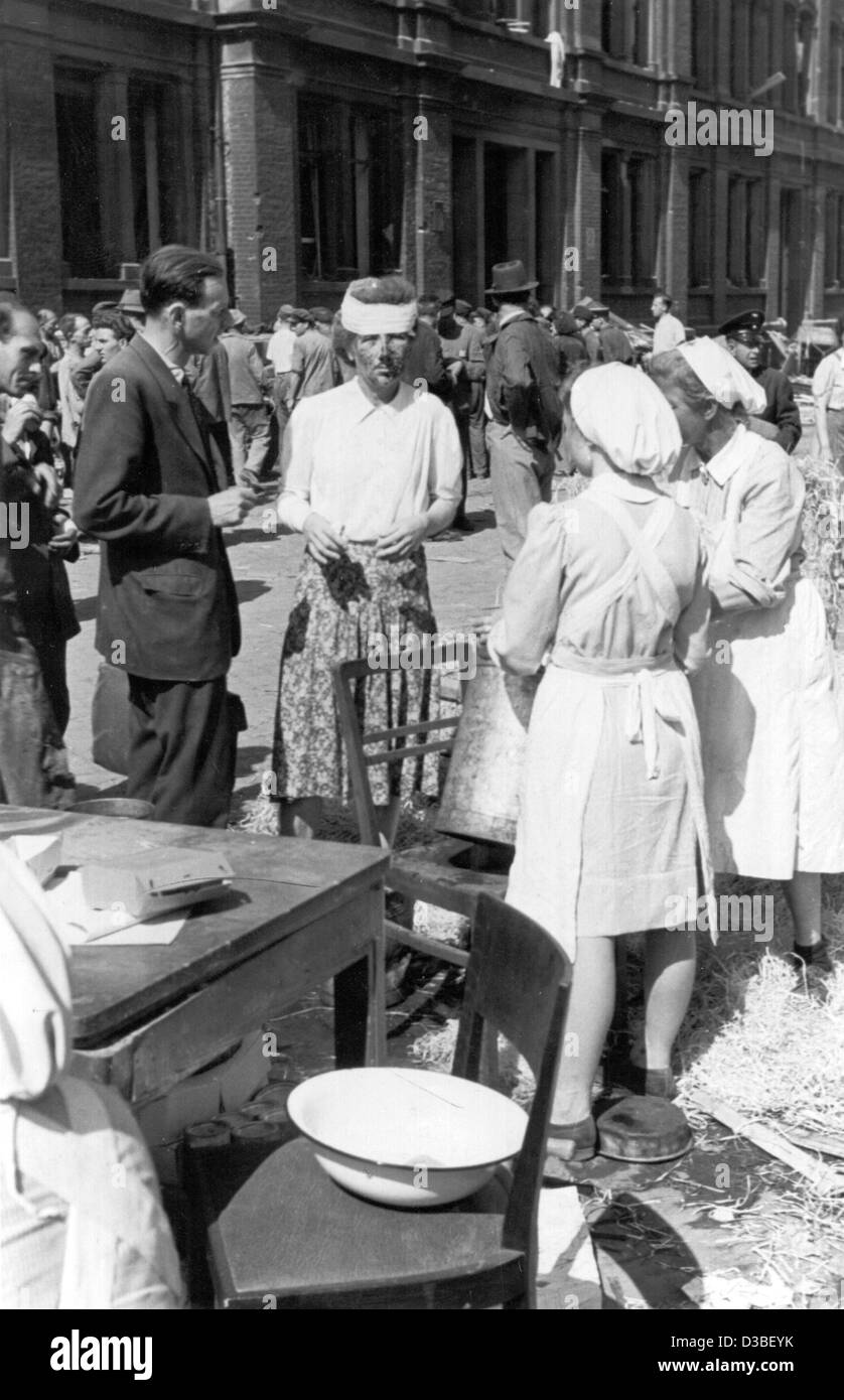 (dpa files) - An injured woman is helped by nurses at a rough-and-ready field dressing station on the grounds of - Stock Image