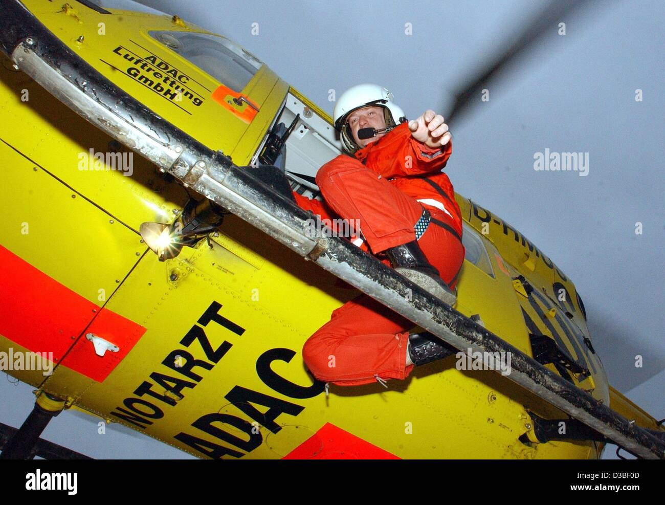 (dpa) - Rescue worker Daniel Gerth of the German auto club ADAC stands on the skids of the rescue helicopter Christoph - Stock Image