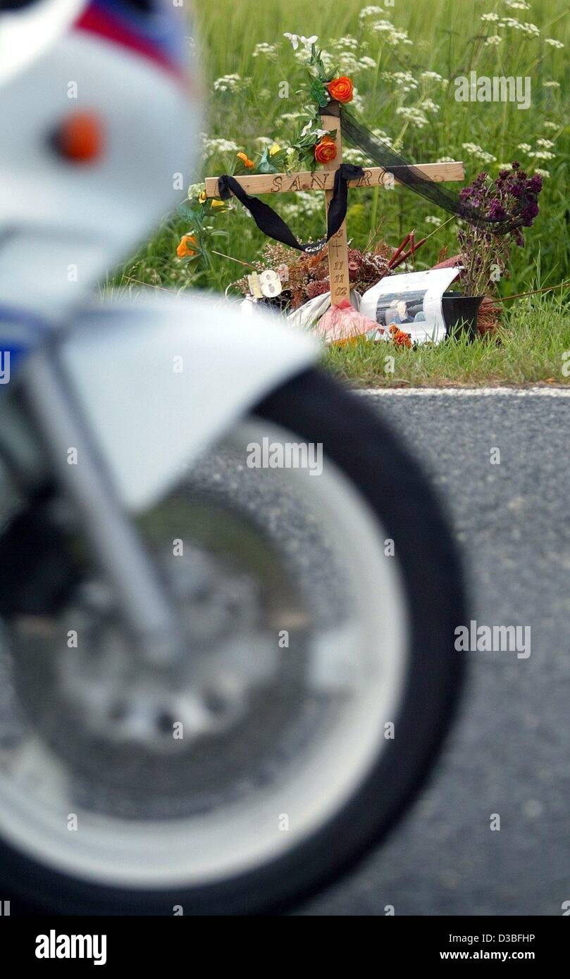 (dpa) - A motorbicycle drives past a wooden cross which indicates the spot of a traffic accidents with deadly outcome - Stock Image