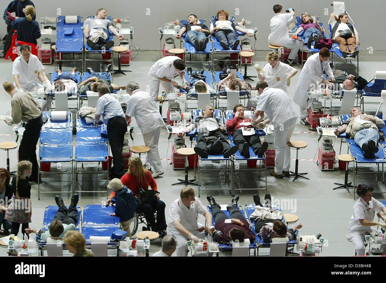 (dpa) - A group of volunteers relaxe on pallets while they donate blood in the Westfalenhalle in Dortmund, Germany, - Stock Image